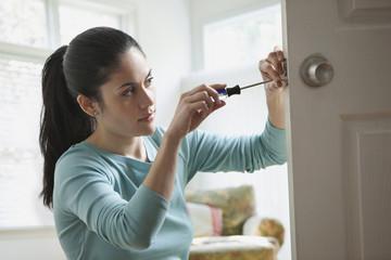 Mixed race woman fixing door