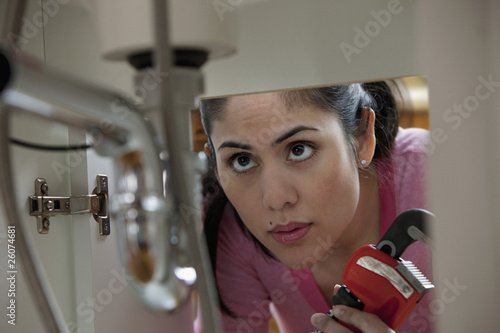 Mixed race woman holding wrench and looking at pipes
