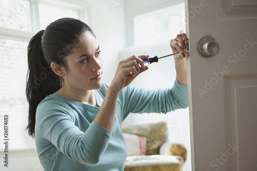 Mixed race woman fixing door