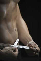 Mixed race man measuring waist