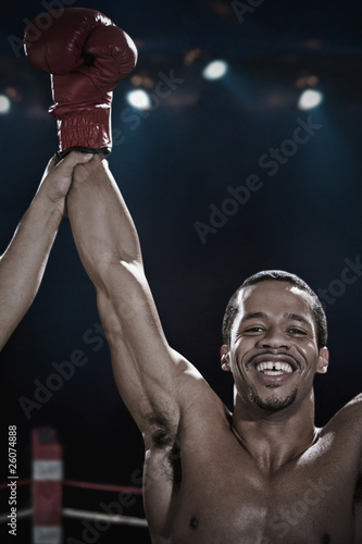 Smiling mixed race boxer with arms raised in boxing ring