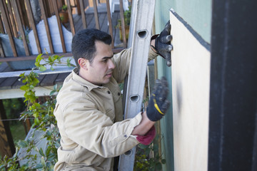 Hispanic man fixing siding of house