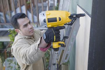 Hispanic man drilling siding on house