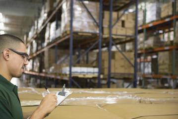 Hispanic man completing paperwork in warehouse