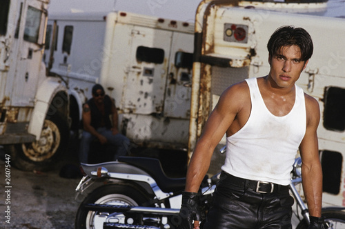 Hispanic man in front of motorcycle