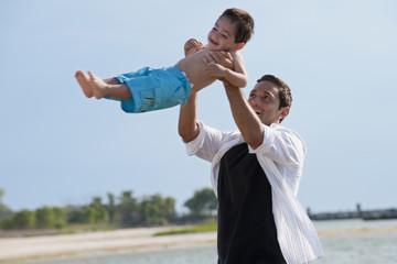 Hispanic father lifting young son