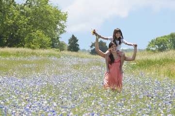 Mother carrying daughter on shoulders in field of wildflowers