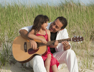 Father and daughter playing guitar on beach