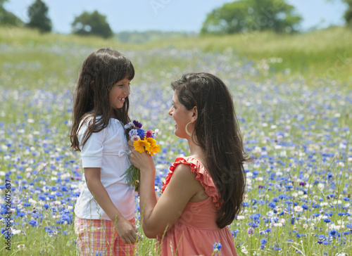 Mother and daughter in field of wildflowers