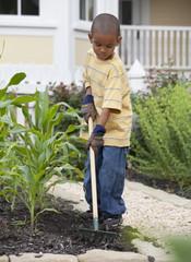 Mixed race boy gardening