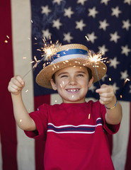 Mixed race boy holding sparklers in front of American flag