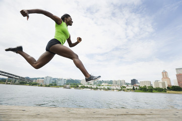 African woman leaping next to river