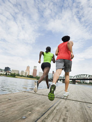 Couple running on urban boardwalk along river