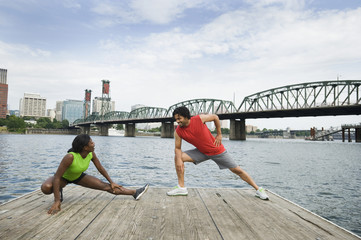 Couple stretching on urban boardwalk along river