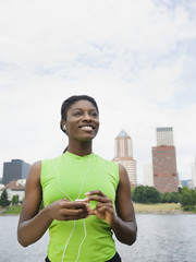 African woman listening to headphones with city in background