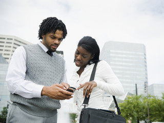 Businessman and businesswoman looking at cell phone in city