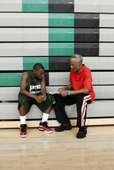 African coach reviewing plays with basketball player