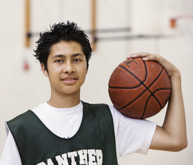 Mixed race basketball player holing ball in gym