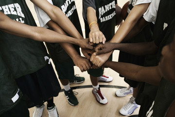 Basketball team putting fists together in huddle