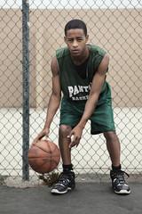African basketball player dribbling ball near fence