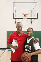 African basketball player and coach hugging in gym