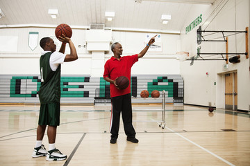 African coach guiding basketball player in gym