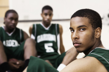 Serious African basketball player sitting in gym