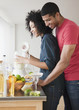 Couple mixing margaritas in kitchen