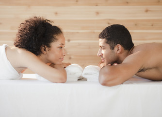 Couple laying face to face on massage table