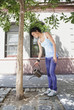 Mixed race woman watering tree on urban sidewalk