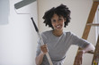 Mixed race woman holding paint roller and leaning on ladder