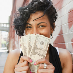 Mixed race woman holding twenty dollar bills