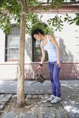 Mixed race woman watering tree on urban sidewalk