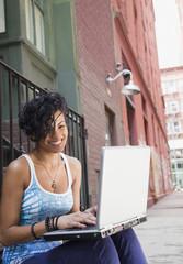 Mixed race woman using laptop on urban sidewalk