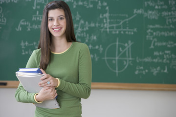 Mixed race teenage girl holding books in classroom