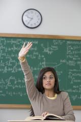 Mixed race teenage girl raising hand in classroom