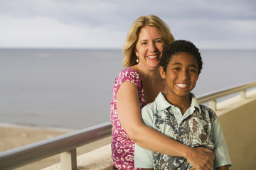 Woman hugging boy on balcony overlooking beach