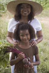 African mother and daughter holding beets in garden