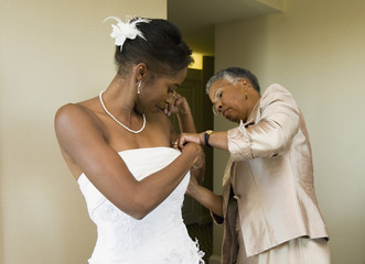 African mother helping bride with wedding dress