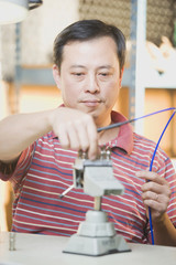 Asian technician working with machinery