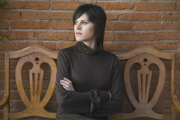 Frustrated Hispanic woman sitting on bench