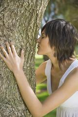 Hispanic woman hugging tree trunk