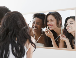 Friends applying makeup in mirror