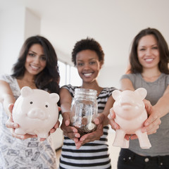Friends holding out glass jar and piggy banks