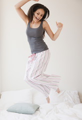 Mixed race woman jumping on bed