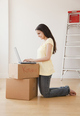 Mixed race woman using laptop on cardboard boxes