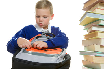 young boy packing his school bag