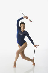 Mixed race gymnast performing with batons