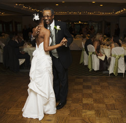 African bride and father dancing at wedding reception