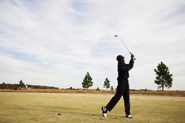 African boy swinging golf club